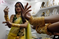 FILE - An Indian model displays gold jewelry during a Jewelry and Gem Fair in Hyderabad, India,.