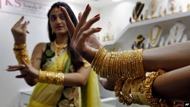 FILE - An Indian model displays gold jewelry during a Jewelry and Gem Fair in Hyderabad, India.