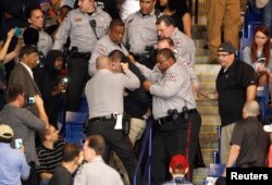 FILE - Police officers forcibly restrain a protester at U.S. Republican presidential candidate Donald Trump's campaign rally in Fayetteville, North Carolina, March 9, 2016.