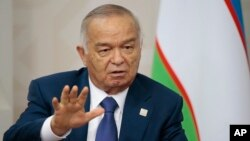 FILE - Uzbekistan's President Islam Karimov gestures while speaking to Russian President Vladimir Putin during the SCO (Shanghai Cooperation Organization) summit in Ufa, Russia, July 10, 2015.