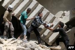 Lực lượng dân phòng và cứu hộ Syria cứu một em bé từ dưới đống đổ nát của một tòa nhà bị phá hủy sau cuộc không kích vào khu phố bị phiến quân chiếm giữ ở phía bắc Aleppo, ngày 28 tháng 4 năm 2016.
