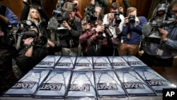 Media photograph copies of President Obama's new $4 trillion budget plan as it arrives on Capitol Hill in Washington, Monday, Feb. 2, 2015. (AP Photo/J. Scott Applewhite)