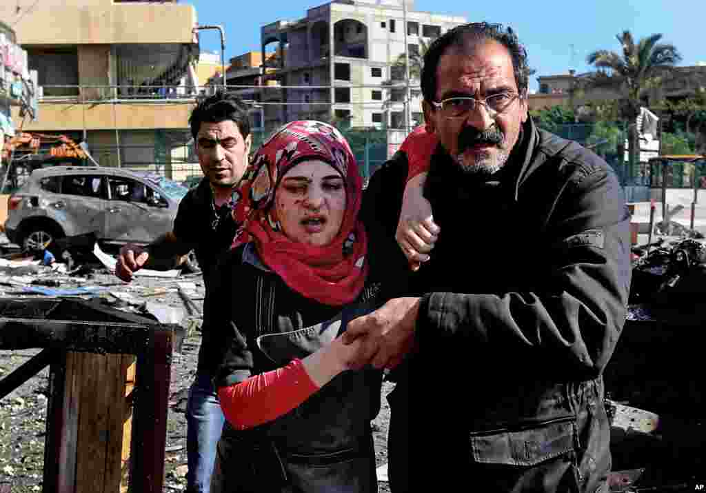 A Lebanese man helps an injured woman, as they pass wreckage from an explosion, near the Kuwaiti Embassy and Iran's cultural center in Beir Hassan, Lebanon.