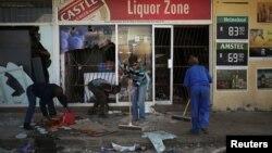 Les habitants nettoient après les manifestations à Coligny, Afrique du sud, le 26 avril 2017.