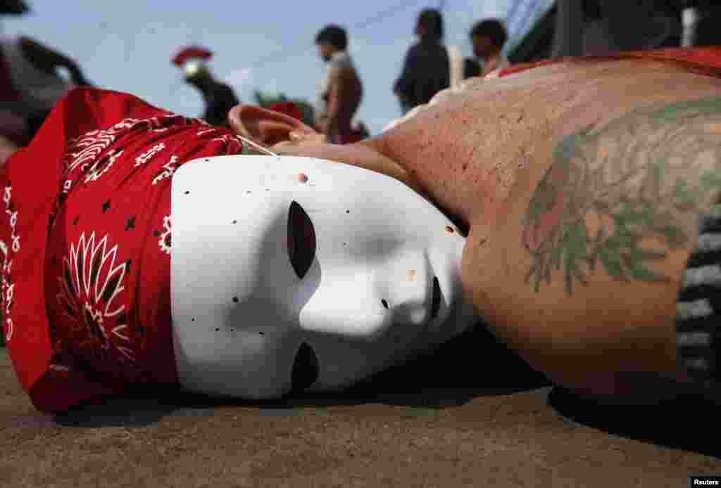 필리핀 마닐라의 성목요일 세족식에서 마스크를 한 연기자가 채찍을 맞고 바닥에 누워있는 퍼포먼스를 하고 있다.