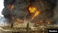 La fumée et les flammes s'échappent d'un pipeline de pétrole en feu après un sabotage par des hommes armés non identifiés à Andoni, Rivers State, Nigeria, 20 décembre 2005.