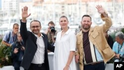 From left, director Andrey Zvyagintsev, actors Maryana Spikav and Alexei Rozin pose for photographers during the photo call for the film Loveless at the 70th international film festival, Cannes, southern France, Thursday, May 18, 2017.