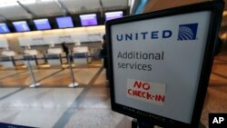 FILE - A piece of tape is affixed to a sign marking an empty line at the United Airlines ticket counter at Denver International Airport, April 16, 2016, in Denver, Colorado. United came under fire for having a passenger dragged off an overbooked flight at Chicago's O'Hare International Airport, April 9, 2017.
