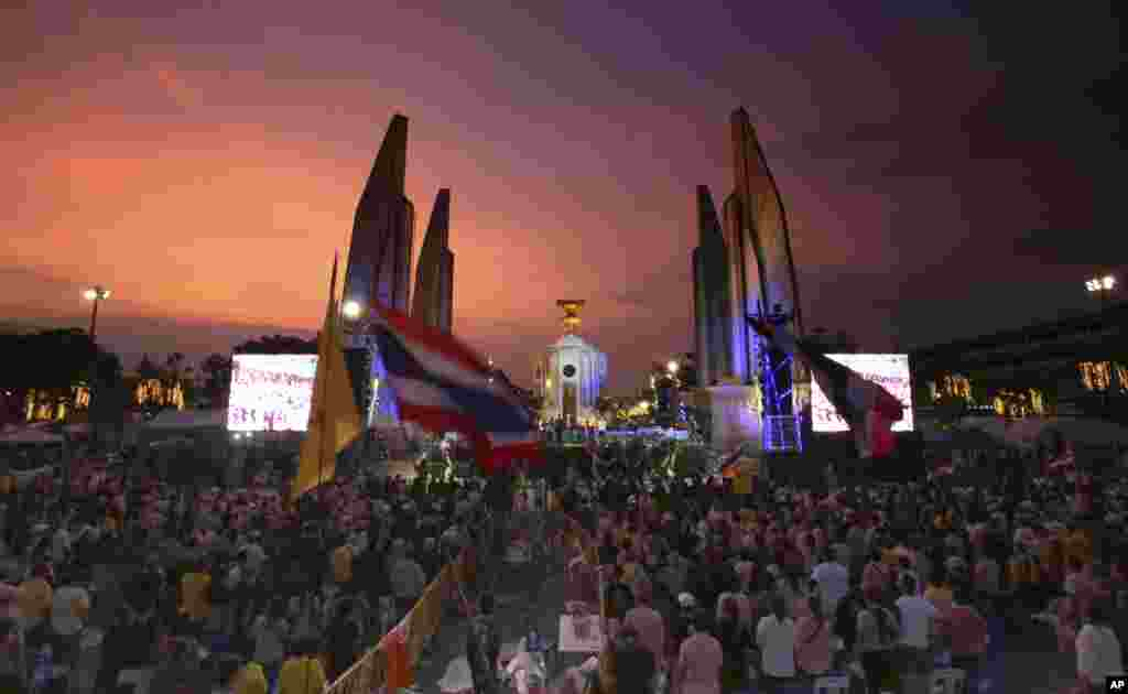 Anti-government protesters stand up to hear the national anthem at the Democracy Monument in Bangkok,  Dec. 6, 2013.
