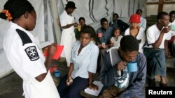 FILE - Cholera patients drink treated water inside an admission ward at Budiriro Polyclinic in Harare, Zimbabwe.