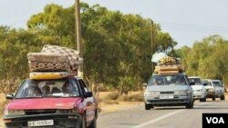 Warga sipil menyelamatkan diri dari bentrokan antara pro dan anti-Gaddafi di Sirte (1/10).