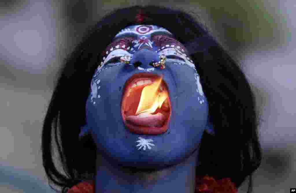 Seorang pria India berpakaian seperti Dewi Hindu Kali memasukkan api ke dalam mulutnya pada perayaan festival Ram Navami (kelahiran Rama) di Allahabad, India.