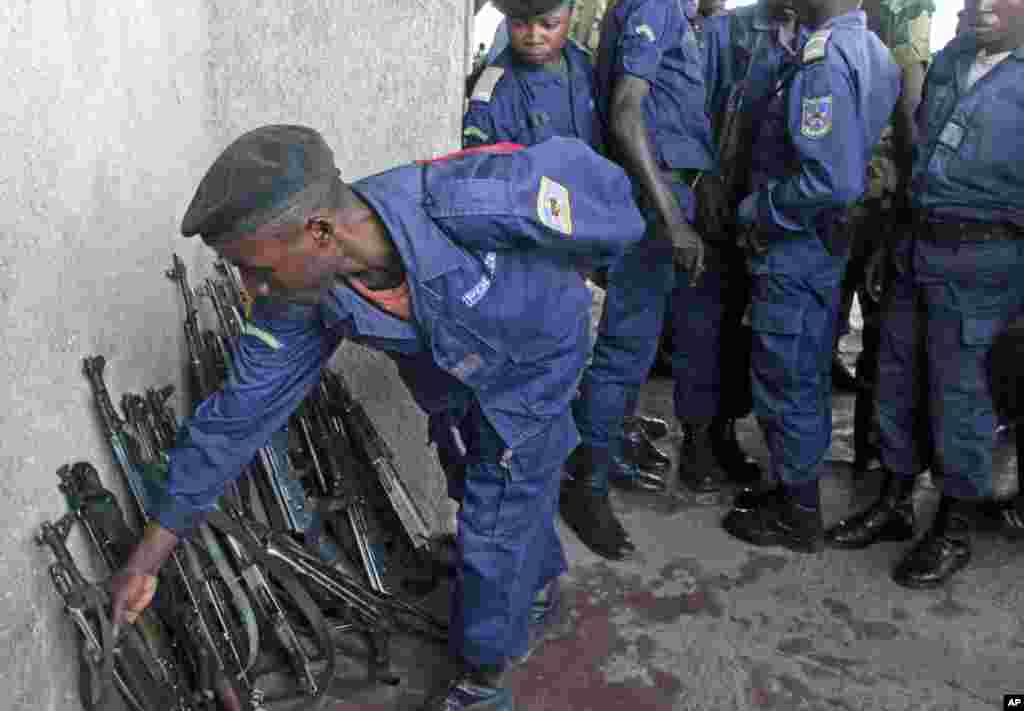 A Congo government policeman hands in his weapon to M23 rebels during an M23 rally in Goma, DRC, November 21, 2012.