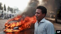 Một người đàn ông than khóc sau khi xe của ông bị các nhà hoạt động đảng Jamaat-e-Islami đốt cháy tại thủ đô Dhaka.