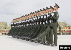 FILE - Soldiers of China's People's Liberation Army march with their weapons during a training session for a military parade to mark the 70th anniversary of the end of World War II, at a military base in Beijing, Sept. 1, 2015.