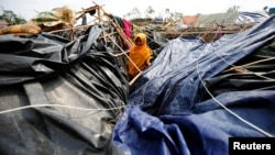 FILE - A young Rohingya refugee stands in her house which has been destroyed by Cyclone Mora at Balukhali Refugee Camp in Cox's Bazar, Bangladesh, May 31, 2017.
