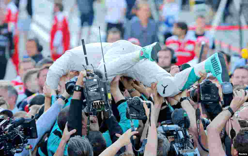 Mercedes F1 driver Nico Rosberg of Germany celebrates a victory with team members after the Russian Grand Prix.
