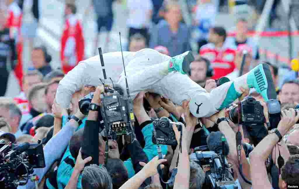 Pembalap F1 Mercedes, Nico Rosberg, dari Jerman merayakan kemenangannya bersama anggota timnya setelah menyelesaikan Grand Prix Rusia.