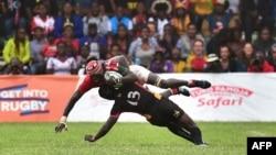 Le centre des Cranes de l'Ouganda, Michael Okorach (en bas), aux prises avec l'attaquant kenyan Oliver Mang'eni lors du match des qualifications pour la Coupe du Monde de Rugby de l'Union Japonaise-2019 - entre le Kenya et l'Ouganda, Nairobi, 7 juillet 20