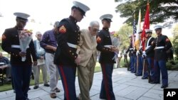 Former American prisoner of war Joseph Demott, 97, center, of Lititz, Pennsylvania, helped by U.S. soldiers, walks to offer flowers at the Commonwealth War Graves in Yokohama, near Tokyo, Oct. 12, 2015.