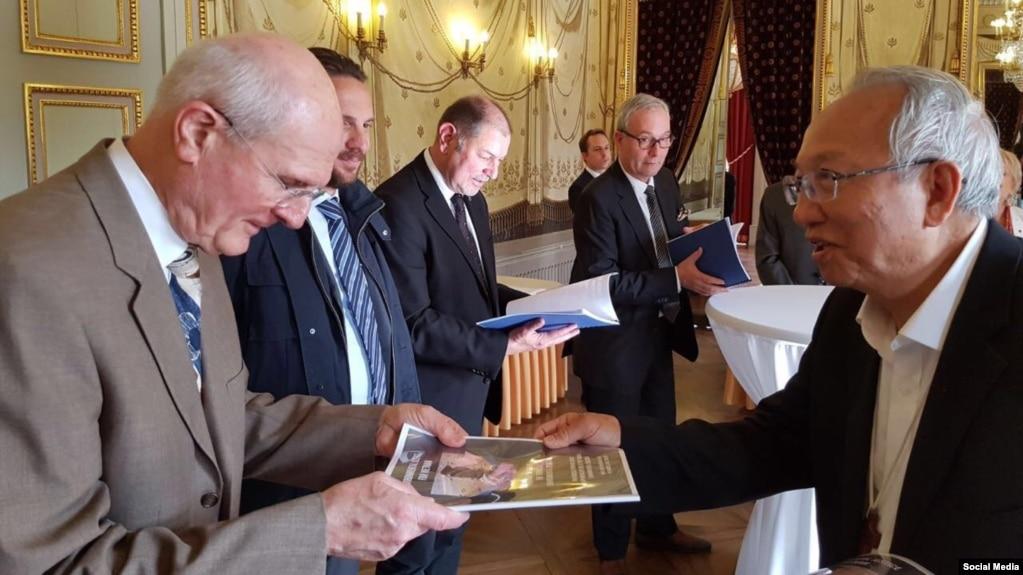 Giám Mục Nguyễn Thái Hợp trao thỉnh nguyện thư cho cựu thị trưởng Geneva, Michel Rosetti, trong chuyến đi vận động quốc tế về thảm họa Formosa.