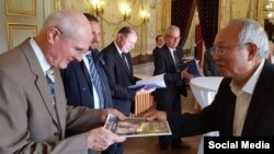 Giám Mục Nguyễn Thái Hợp trao petition đến cựu thị trưởng Geneva, Michel Rosetti, trong buổi tiếp tân do đương kim thị trưởng Guillaume Barazzone và các chính khách khác cùng tổ chức.