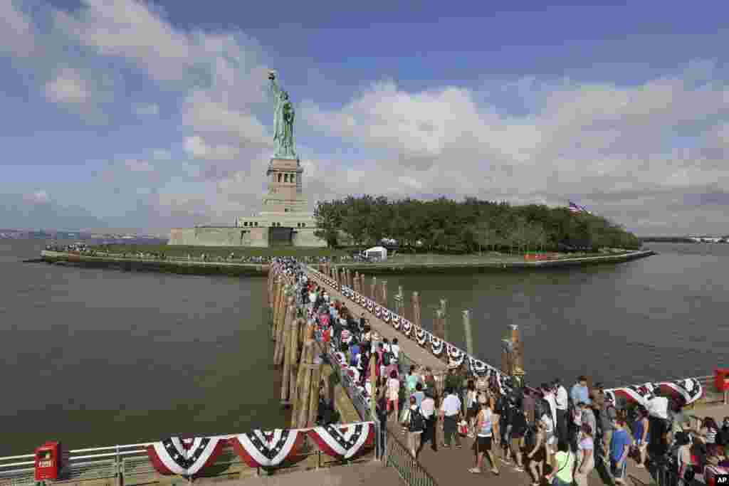 Visitors to the Statue of Liberty disembark onto Liberty Island from the first ferry to leave Manhattan, July 4, 2013.