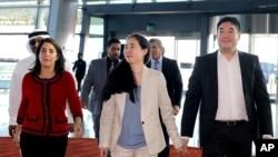 Dubes AS untuk Qatar Dana Shell Smith (kiri) mengantarkan pasangan Matt dan Grace Huang di bandara Doha, Qatar (3/12).