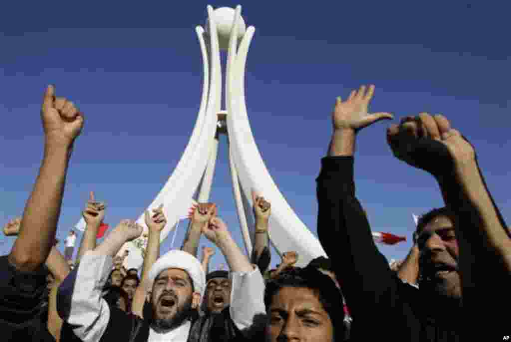 Bahraini protesters chant slogans at the Pearl roundabout soon after the military and police pulled out in Manama, February 19, 2011. The deputy chief of armed forces has ordered the military to withdraw from the streets of the capital. (AP Image)