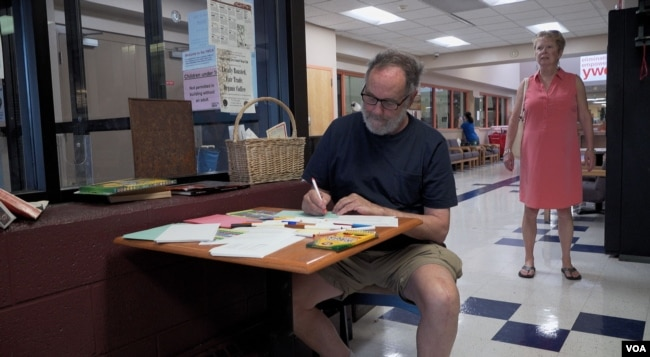 Gettysburg resident Donald Marritz writes a message of encouragement in Spanish for migrant children housed in a Baltimore, Maryland, facility. (M. Kornely/VOA)