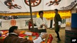 ຜຸ້ຍິງຄົນນຶ່ງປ່ອນປັດຂອງລາວ ຢູ່ສະຖານີປ່ອນບັດ ໃນເມືອງຫລວງ Thimphu ຂອງພູຖານ
