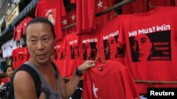 A Korean tourist buys a tee-shirt at a shop in Rangoon on March 29, 2012.