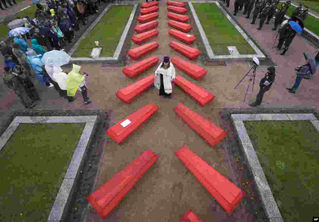 An Orthodox priest conducts a burial ceremony of 228 Soviet soldiers killed during World War II, in a memorial cemetery at Nevsky Pyatachok near Kirovsk, Russia.