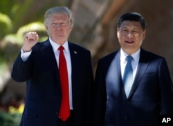FILE - President Donald Trump and Chinese President Xi Jinping pause for photographs at Mar-a-Lago, April 7, 2017, in Palm Beach, Fla.