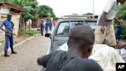 Des cadavres sont disposés à l'arrière d'un pick up alors que la police patrouille dans les rues du quartier Nyakabiga de Bujumbura, le 12 décembre 2015. (AP Photo)