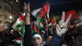 Palestinians celebrate as they watch a screen showing the U.N. General Assembly vote on a resolution to upgrade the status of the Palestinian Authority to a non-member observer state, in the West Bank city of Ramallah, Nov. 29, 2012.