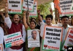 FILE - Members of Bharatiya Janata Party Minority Morcha shout slogans during a protest against the conviction of a retired Indian naval officer Kulbhushan Jadhav, in Mumbai, India.