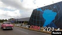 Un auto pasa frente al sitio donde se desarrolla la cumbre de la CELAC, en La Habana.