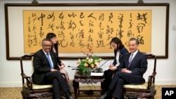 世界衛生組織總幹事譚德塞博士和中國外交部長王毅2018年7月2日在北京外交部會晤之前合影。他們身後的書法是唐代詩人王勃的詩。