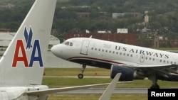 Un avión de US Airways despega detras de otro de American, en el Aeropuerto Nacional Ronald Reagan de Washington.