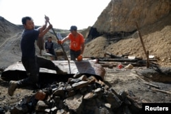 FILE - Uuganbaatar, left, and his colleagues work on extracting coal from a primitive mine in Nalaikh, one of the nine districts of Mongolian capital Ulaanbaatar, Mongolia, June 29, 2017.