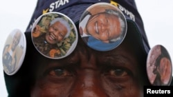 A street vendor sells Nelson Mandela-themed buttons outside the house where the anti-apartheid icon once lived in the township of Soweto, Dec. 9, 2013.