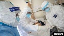 2020年2月16日,身穿防護服的武漢紅十字會醫院的醫護人員在照看一位被隔離的新冠病毒感染病人。
