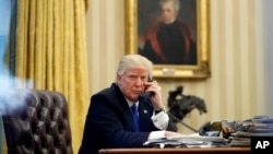 FILE - President Donald Trump speaks on the phone with Prime Minister of Australia Malcolm Turnbull in the Oval Office of the White House, Jan. 28, 2017.