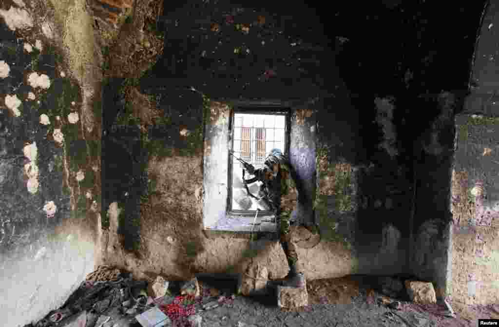 A Free Syrian Army fighter looks through a window of a damaged house in Old Aleppo, Dec. 15, 2013.