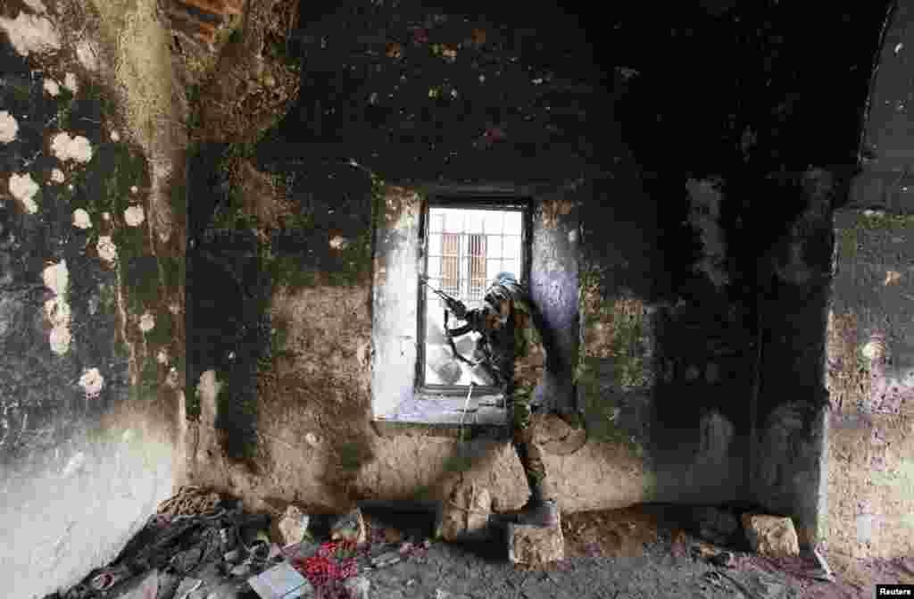 یک عضو ارتش آزاد سوریه در خانه ای در بخش قدیمی شهر حلب که در اثر حملات آسیب دیده است.