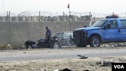 Petugas membersihkan lokasi serangan bom bunuh diri di luar penjara kota Taji, sebelah utara Baghdad (28/11).
