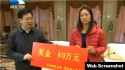 Chinese tennis star Li Na accepts a check from Hubei Communist Party chief Li Hongzhong Tuesday, January 28, 2014 following her weekend championship win at the 2014 Australian Open.