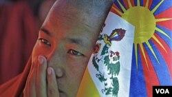 Seorang biarawan Budha memegang bendera Tibet. Aksi bakar diri sebagai bentuk protes terhadap pemerintahan Tiongkok akhir-akhir ini meningkat.