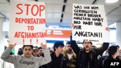 FILE - People take part in a demonstration against the deportation of some 50 Afghan refugees from Munich airport, southern Germany, Feb. 22, 2017. The Afghan government is asking the Trump administration to halt the deportation of Afghan nationals in the United States.